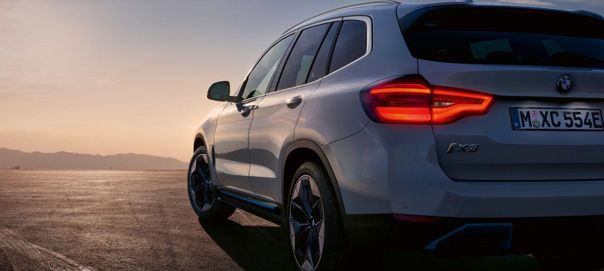BMW iX3 G08 2020 Mineralweiß metallic Dreiviertel-Heckansicht auf Straße